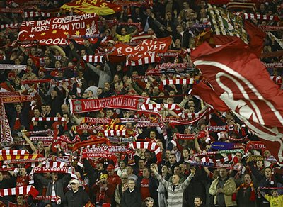 Liverpool fans bearing their scarves aloft.