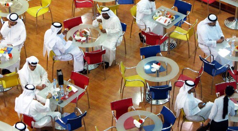 Gentlemen making in excess of $1 million per year dine in an Abu Dhabi restaurant.