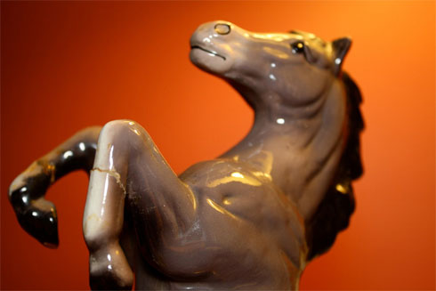 A rearing, cracked, ceramic warhorse