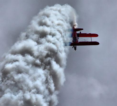 A biplane roars the clouds